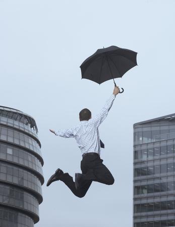 high flown: Businessman jumping for joy outdoors LANG_EVOIMAGES