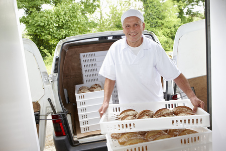 assembled: Chef carrying trays of bread to van