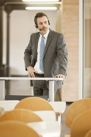 Businessman wearing headset at podium LANG_EVOIMAGES