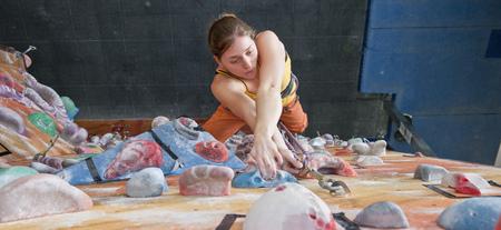 rockclimber: Woman climbing indoor rock wall