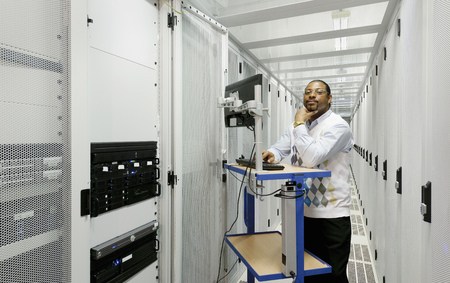 corridors: Businessman using computer with servers