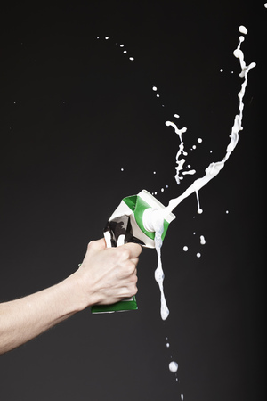 spattered: Hand squeezing carton of milk