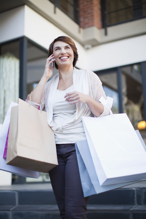 Woman on cell phone with shopping bags
