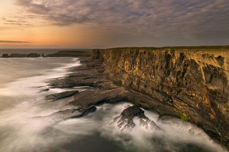 Fog rolling up to rocky coastal cliffs LANG_EVOIMAGES