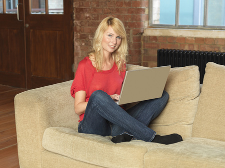 uses: Smiling woman using laptop on sofa