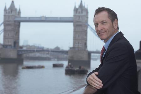histories: Businessman overlooking urban river