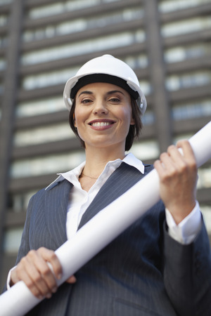 executive helmet: Businesswoman with blueprints outdoors