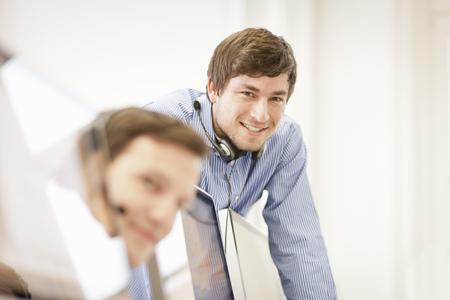 handsfree telephones: Businessman wearing headset in office