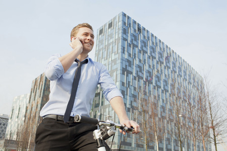 Businessman riding bicycle outdoors LANG_EVOIMAGES
