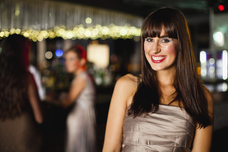 spirited: Smiling woman standing in bar