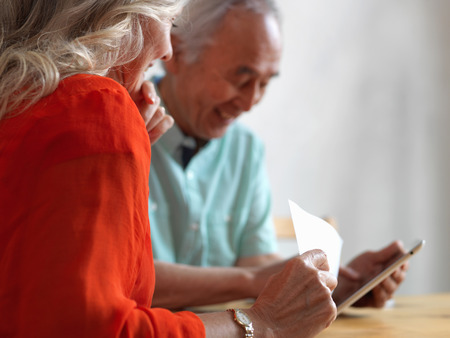 Older couple reading mail in kitchen