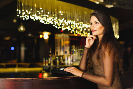 welldressed: Smiling woman standing at bar