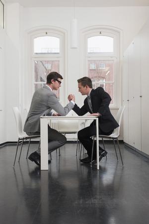 Businessmen arm wrestling in office LANG_EVOIMAGES