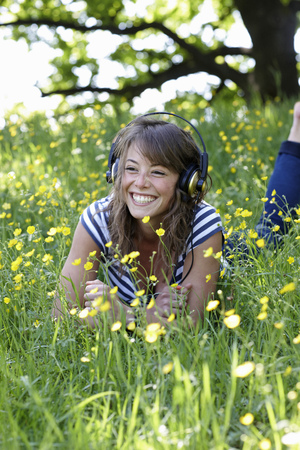 musically: Woman listening to headphones in grass LANG_EVOIMAGES