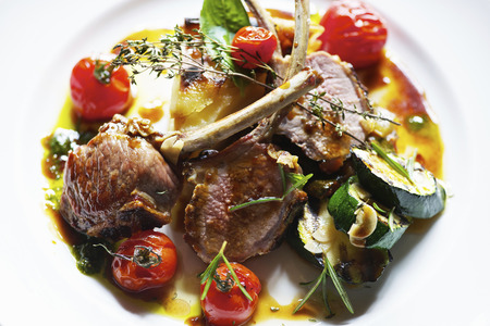 Plate of lamb cutlets with tomatoes