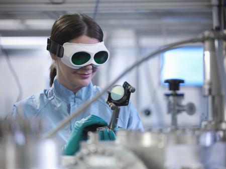 experimentation: Scientist using laser mirror in lab