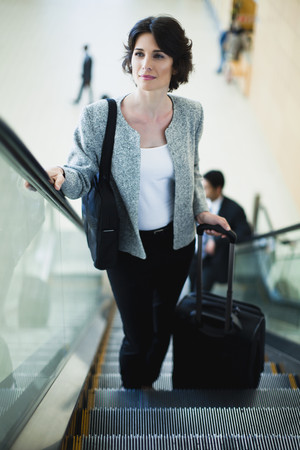 Businesswoman riding escalator LANG_EVOIMAGES