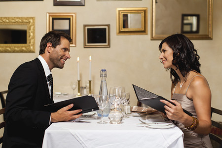 welldressed: Couple examining menus in restaurant