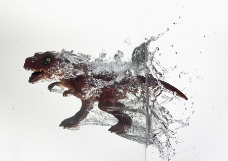 Toy dinosaur plunging into water LANG_EVOIMAGES