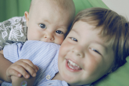 cherished: Baby boy and brother playing on couch LANG_EVOIMAGES