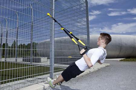leaning by barrier: Man working out in industrial area