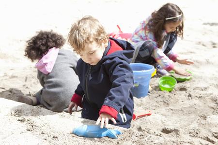 agachado: Niños jugando con la arena en el patio de recreo LANG_EVOIMAGES