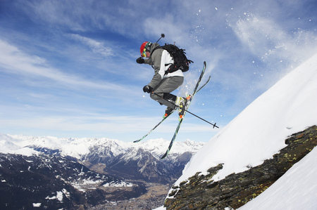 southern european descent: Skier jumping off snowy slope