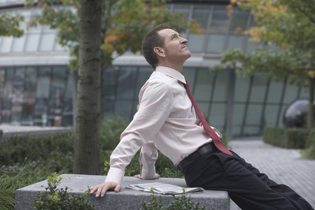 whimsy: Businessman relaxing in urban park