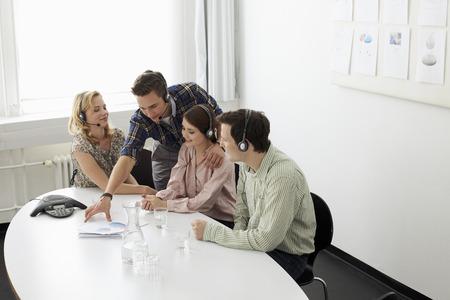 handsfree telephones: Business people in headsets in meeting