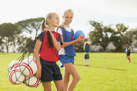 Girl carrying soccer balls on pitch LANG_EVOIMAGES
