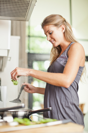 refreshed: Smiling woman cooking in kitchen