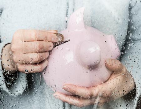 drizzling rain: Woman saving money at rainy window LANG_EVOIMAGES