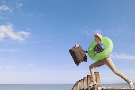 Teenage girl with suitcase on dock LANG_EVOIMAGES