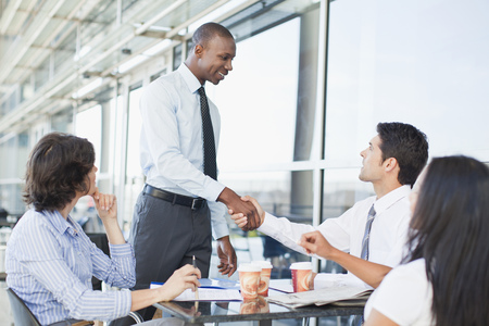 agrees: Business people shaking hands in cafe LANG_EVOIMAGES