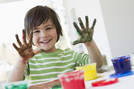 Smiling boy finger painting indoors LANG_EVOIMAGES