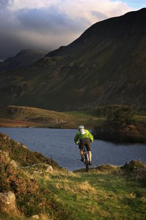 north western european descent: Mountain biker on grassy hillside
