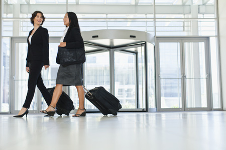 Businesswomen rolling luggage in lobby LANG_EVOIMAGES
