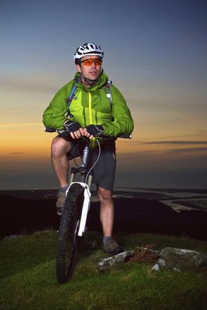 Mountain biker standing on hilltop LANG_EVOIMAGES