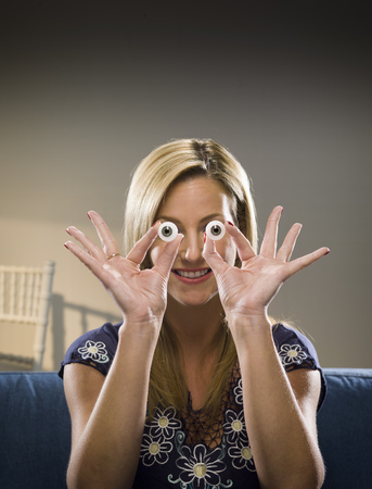 whimsy: Woman holding glass eyes in living room LANG_EVOIMAGES