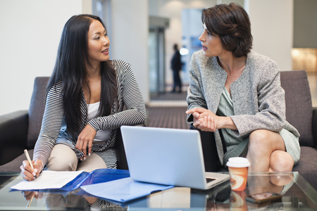 resolving: Businesswomen working together LANG_EVOIMAGES