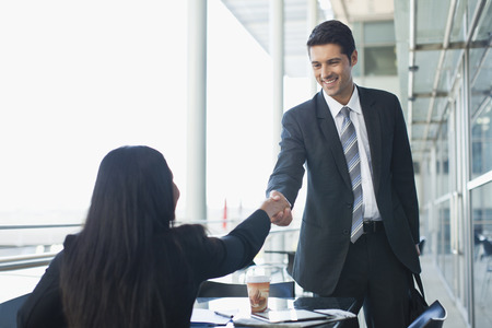 consent: Business people shaking hands in cafe LANG_EVOIMAGES