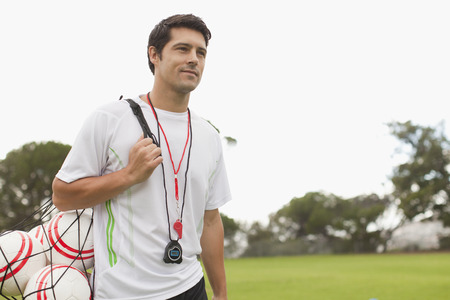 Coach carrying soccer balls on pitch LANG_EVOIMAGES