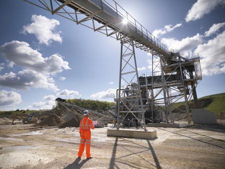 Worker standing under conveyor in quarry
