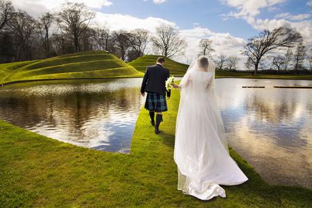 marrying: Newlywed couple walking on grassy bridge