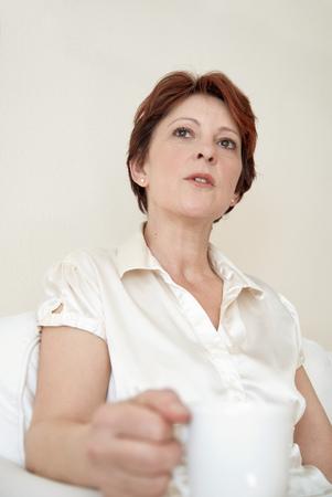 musing: Woman having cup of coffee in armchair