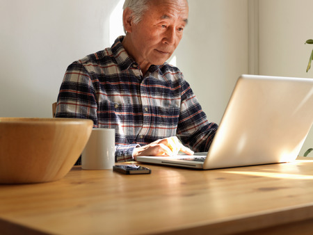 grey eyed: Older man using laptop at table LANG_EVOIMAGES