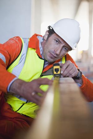 Worker measuring brick on site