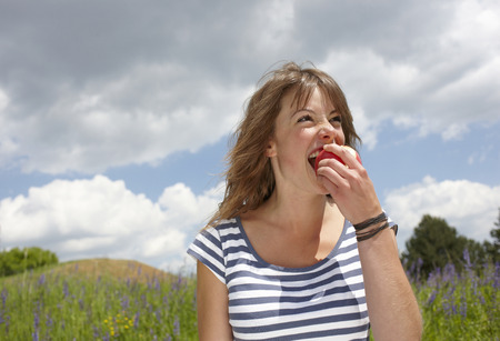 pelo castaño claro: Mujer comiendo manzana al aire libre LANG_EVOIMAGES