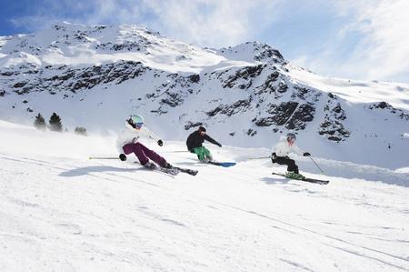 southern european descent: Skiers skiing together on slope LANG_EVOIMAGES