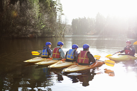 taught man: Teacher talking to students in kayaks